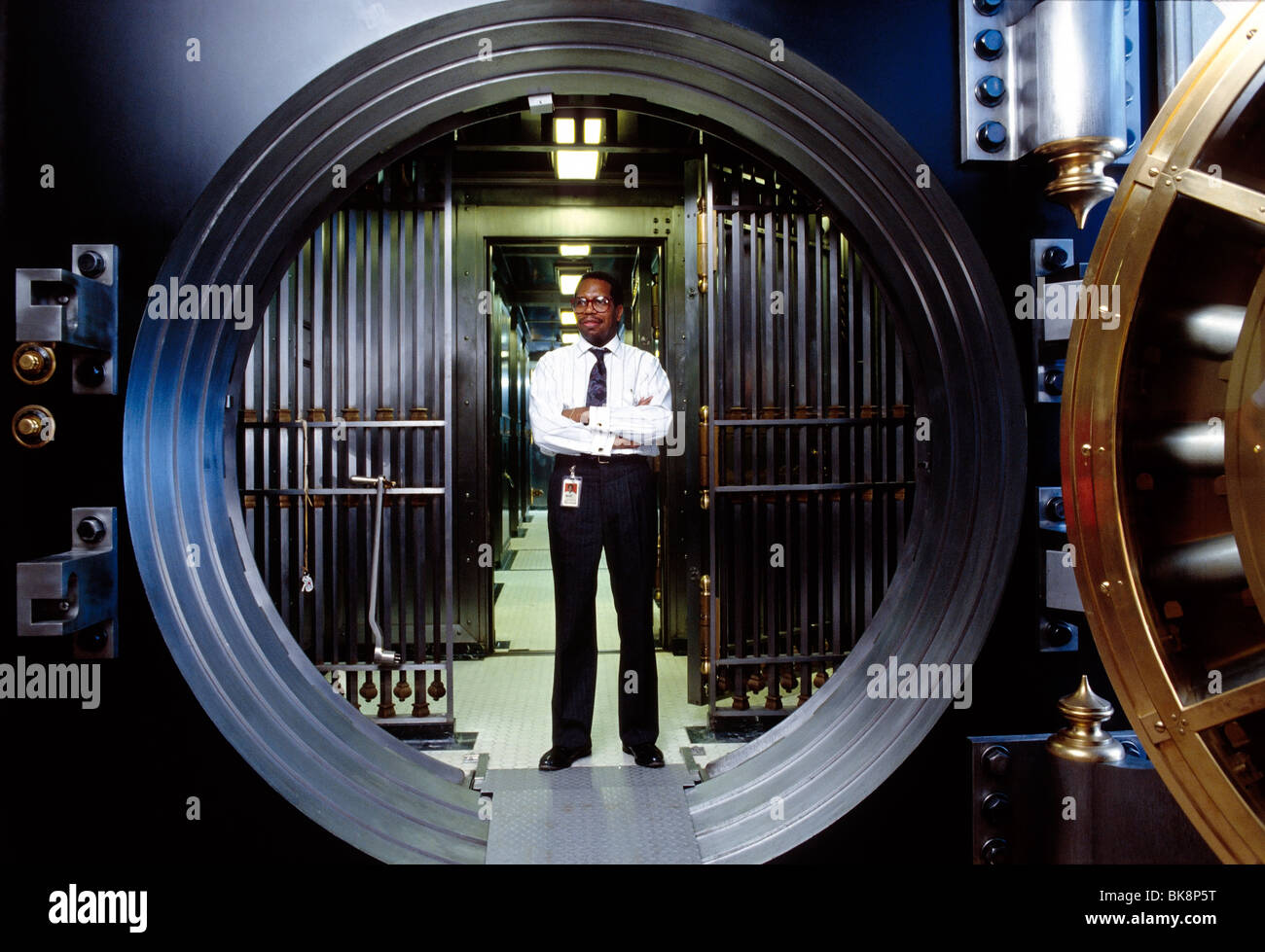 African American bank employee standing in the secure doorway to a large vault - Stock Image