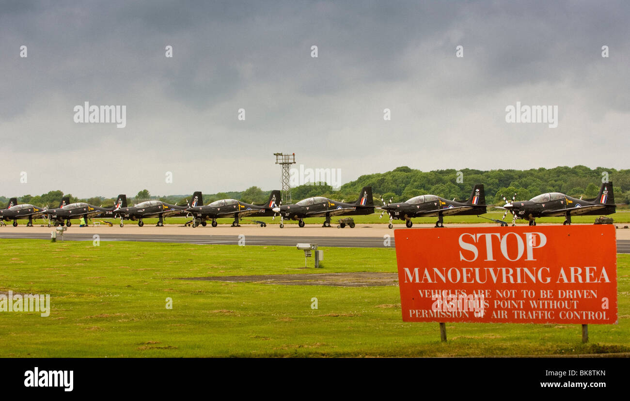 Stationary Tucano planes at RAF Linton-On-Ouse training base, with a Stop warning sign in the foreground - Stock Image