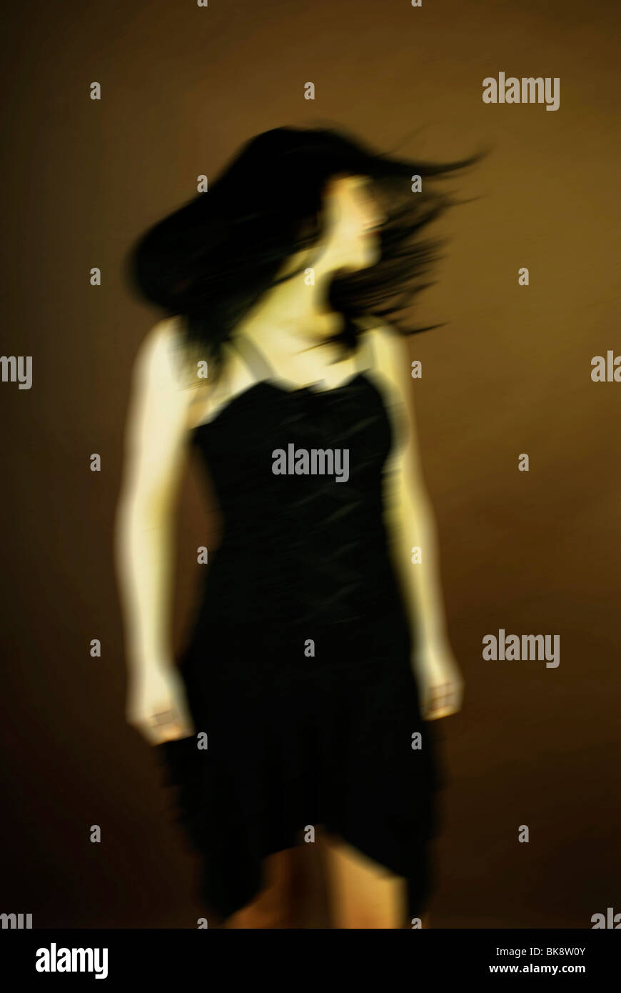 Dark-haired woman tossing her hair, movement - Stock Image