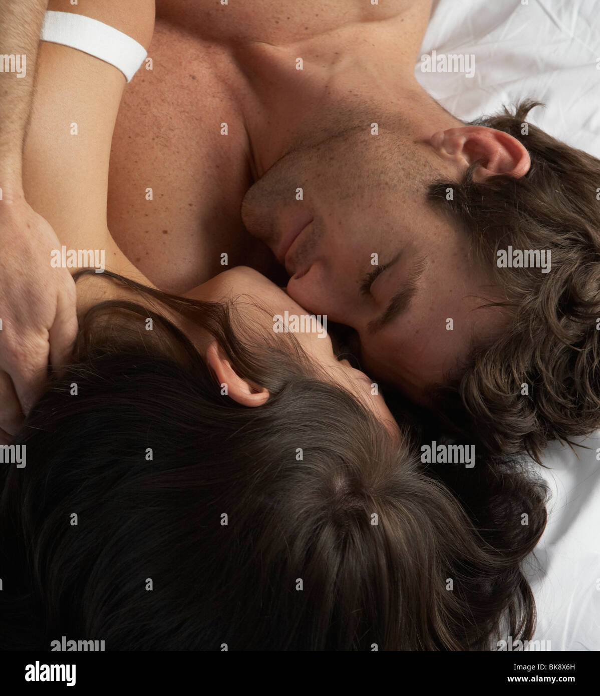 Tight shot of couple in bed embracing - Stock Image