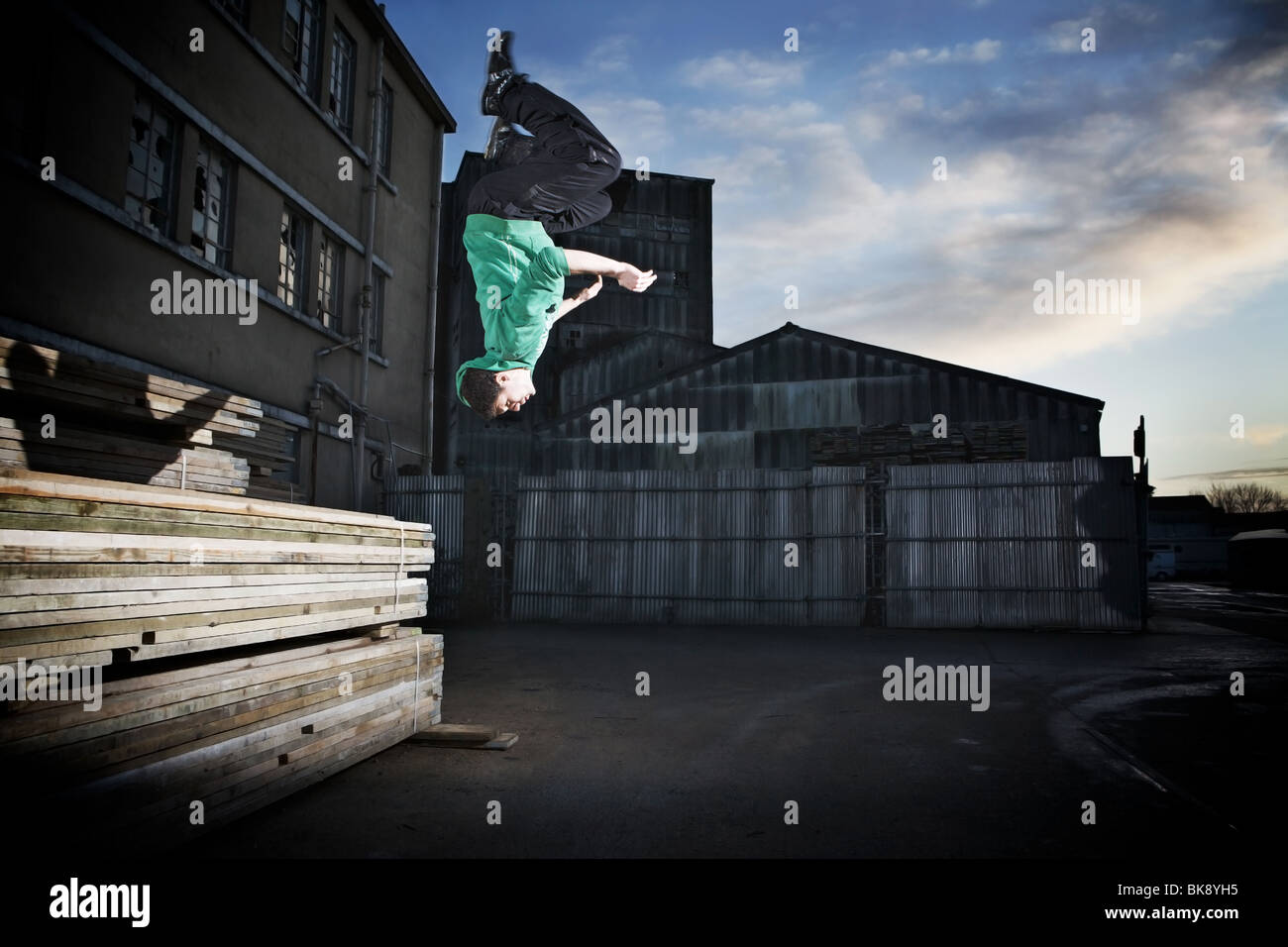 Parkour back flip off wood stack near an abandoned warehouse. - Stock Image