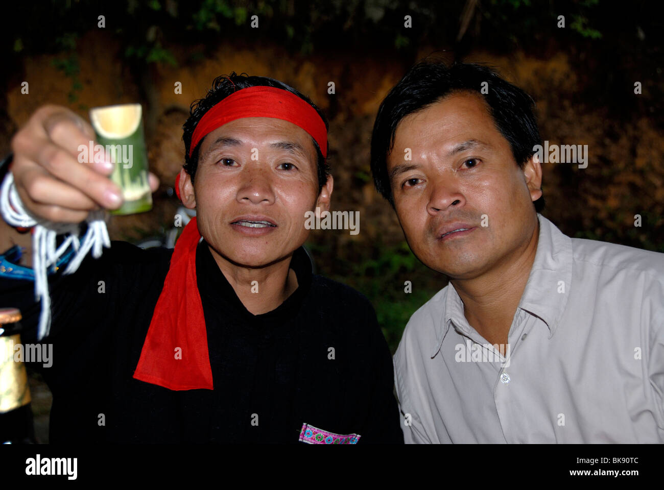 Cheers, men of the Phunoi ethnicity clinking glasses with Lao Lao, Laotian rice wine in bamboo vessels, Phongsali, - Stock Image