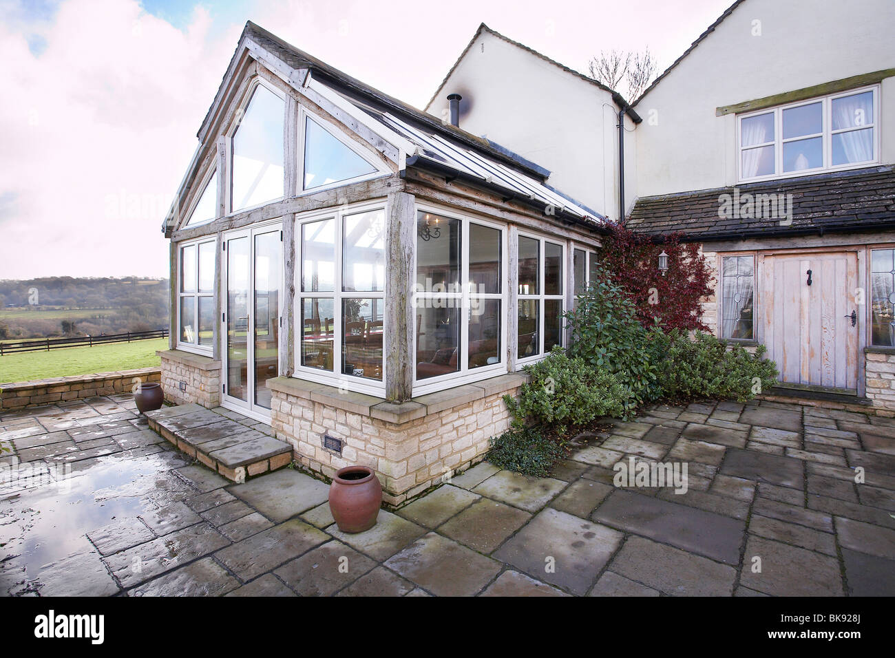 an oak framed orangery type conservatory attached to a house in the