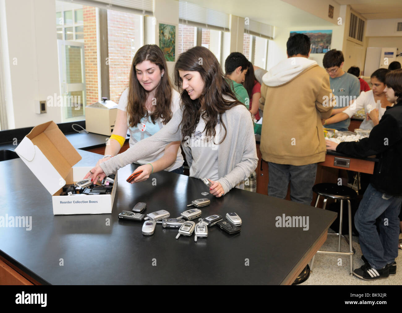 High school environmental club meeting, northern New Jersey. Students are packing old cell phones to send out for - Stock Image
