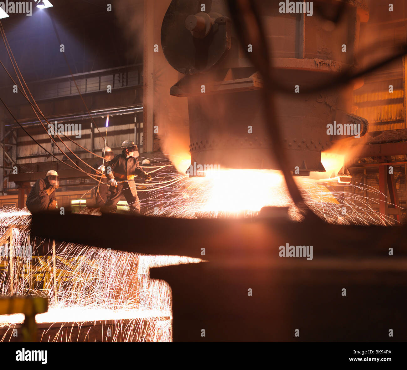 Workers Pouring Molten Steel In Plant Stock Photo