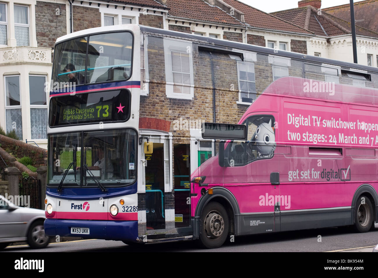 A bus with a digital TV switchover advert all over it, blends into Gloucester Road, Bristol, England. - Stock Image