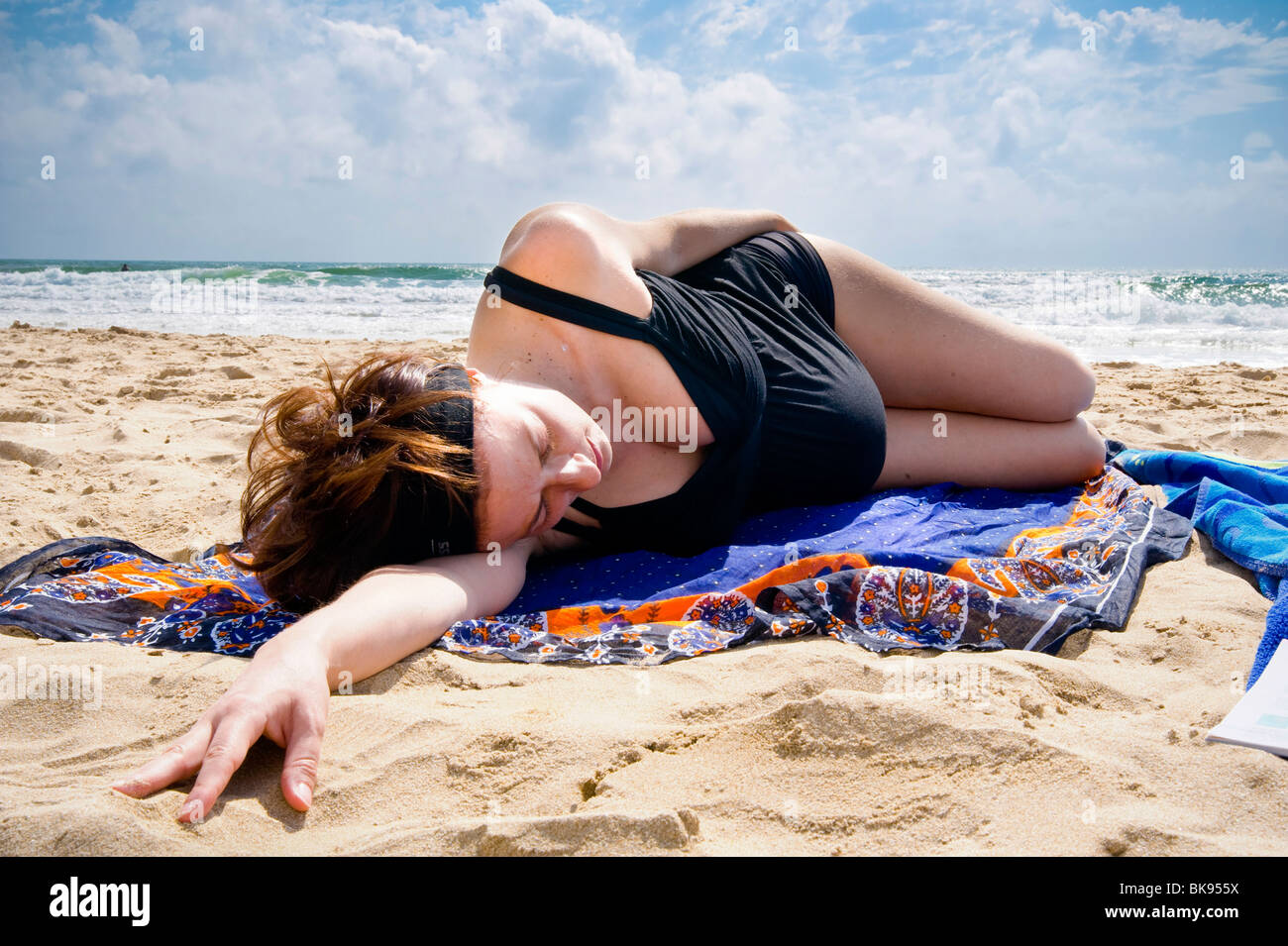 Pregnant woman laying down on the beach by the sea - Stock Image