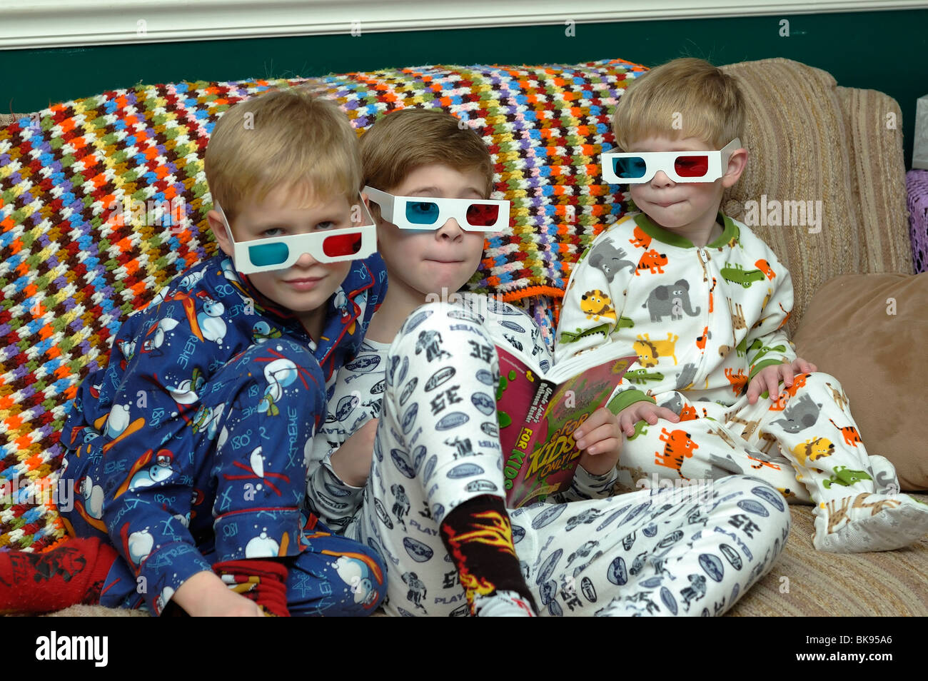 Young brothers wearing pajamas and 3-D glasses - Stock Image