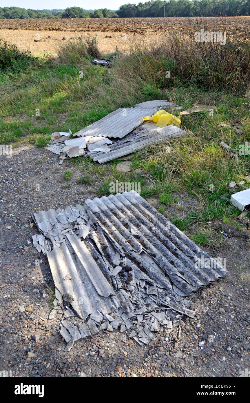 Asbestos sheeting dumped in farmers field beside road - Stock Image