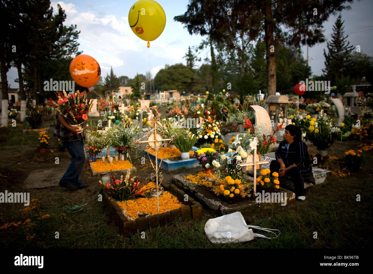 Graves are decorated with flowers and candles in a cemetery in San Gregorio Atlapulco on the outskirts of Mexico - Stock Image