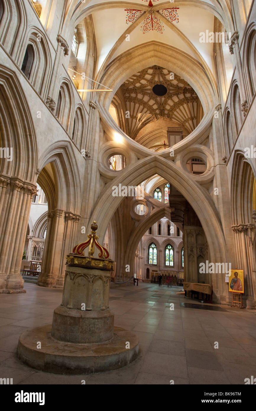 Saxon baptismal font dating from 700 AD and scissor arches in a cathedral, Wells Cathedral, Wells, Somerset, England - Stock Image