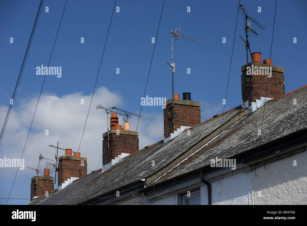 row of red bricked chimney pots on terraced house rooves with tv aerials and overhead telephone wires in the uk - Stock Image
