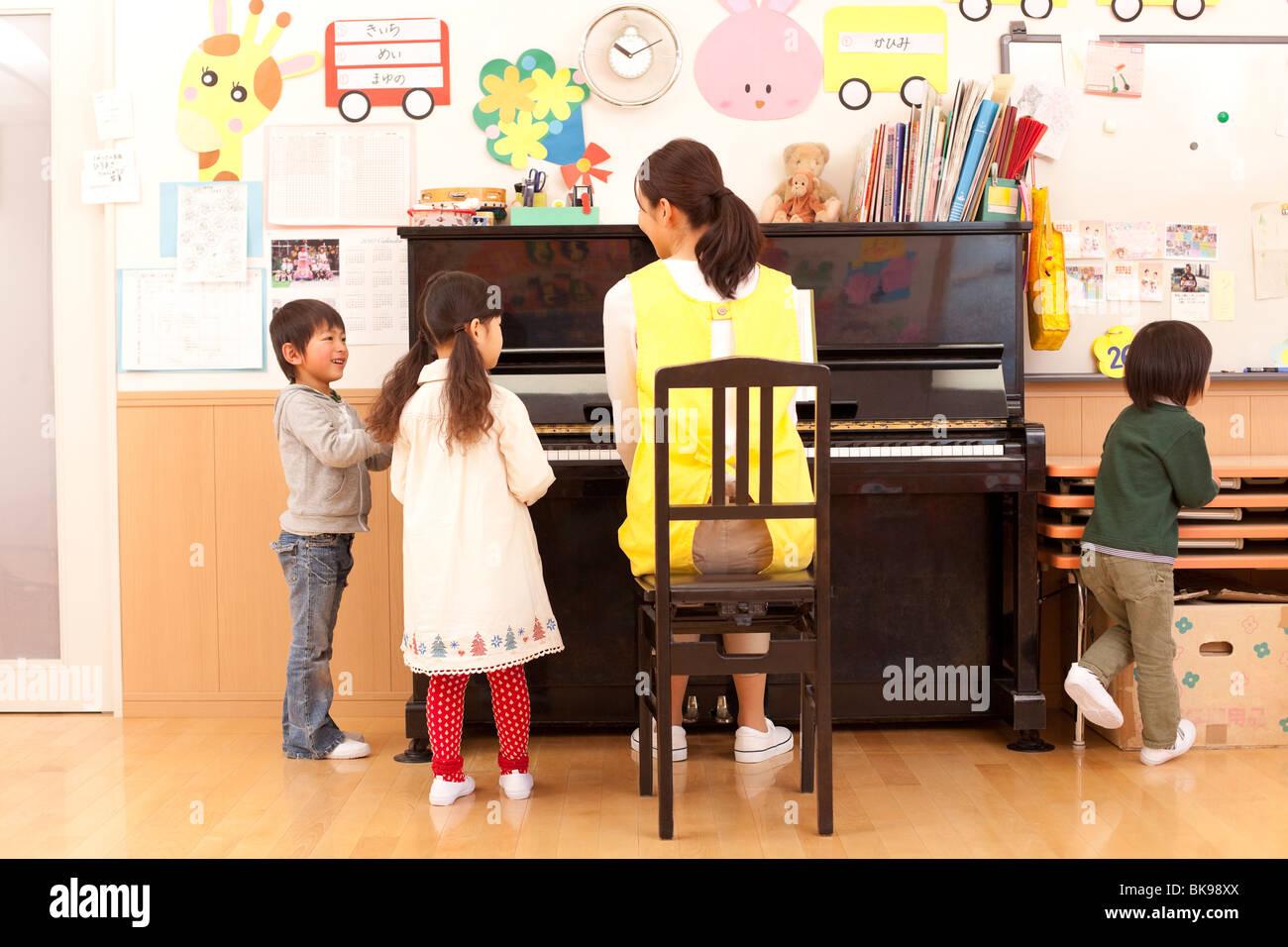Nursery Teacher Playing Piano with Children Stock Photo