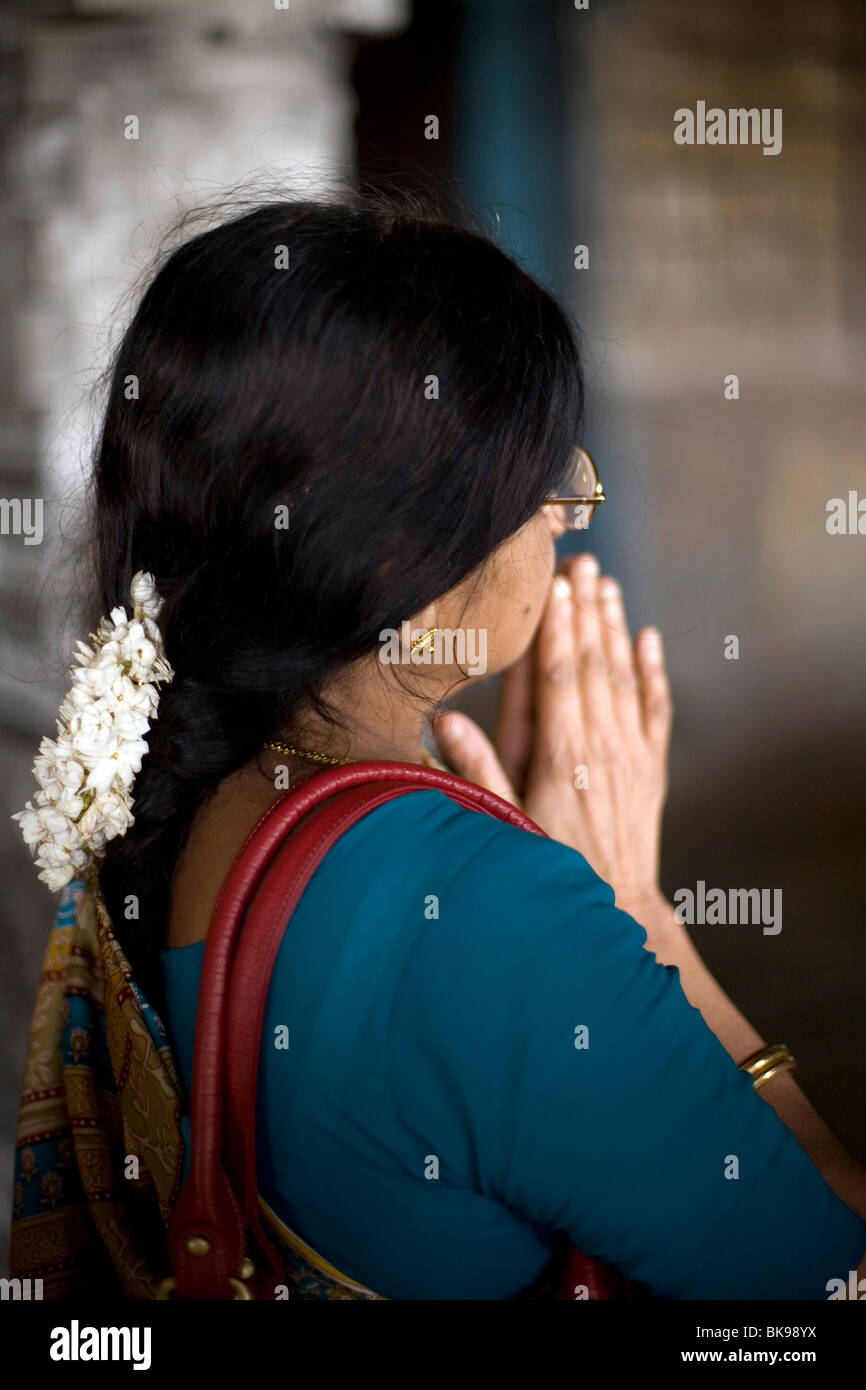 A woman with jasmine flowers in her hair, prays at a shrine in the Murugan Temple in Swamimalai, Tamil Nadu, India - Stock Image