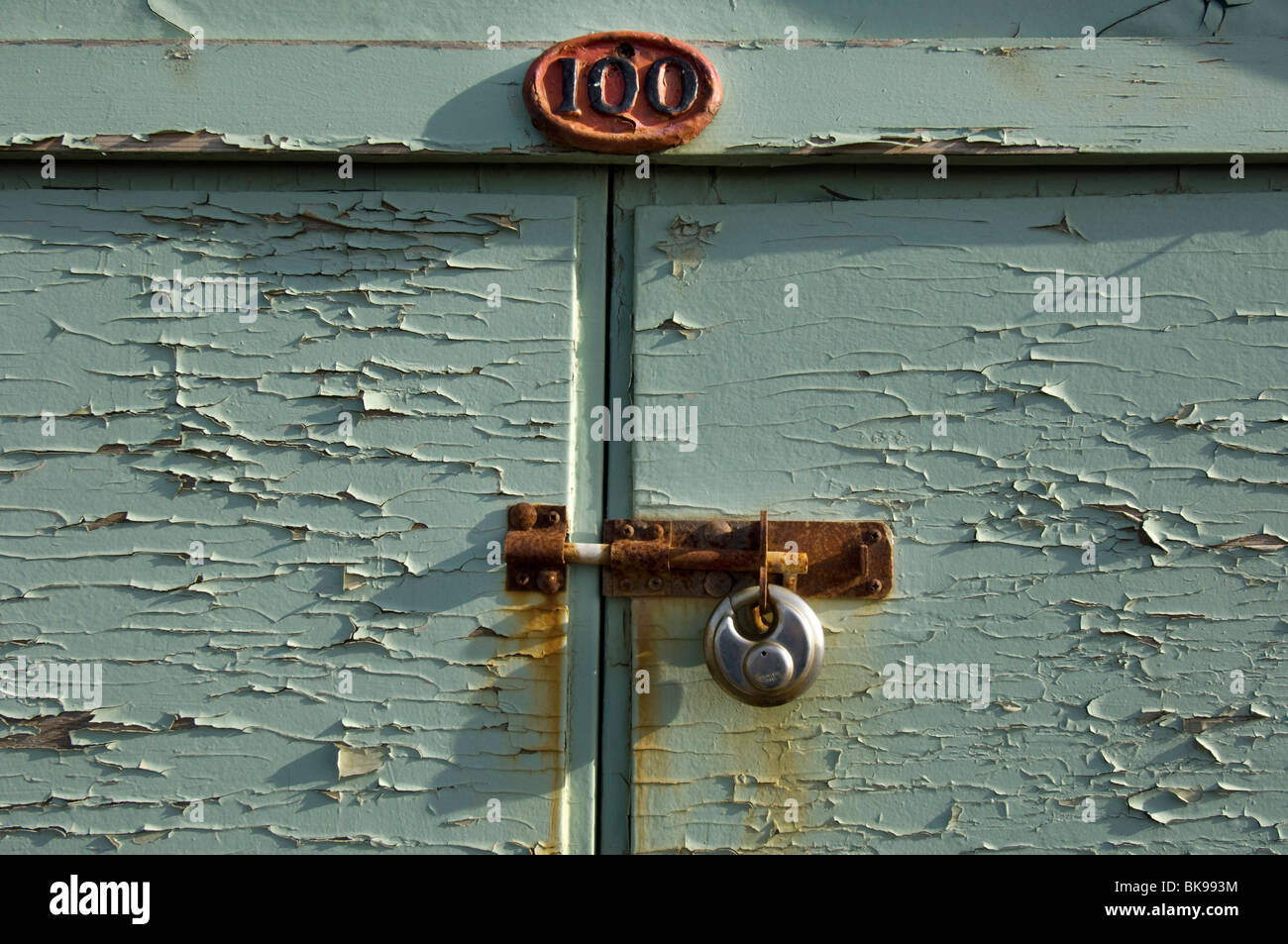 A beach hut, number 100, on Hove Esplanade, with its rusty bolt and padlock. - Stock Image