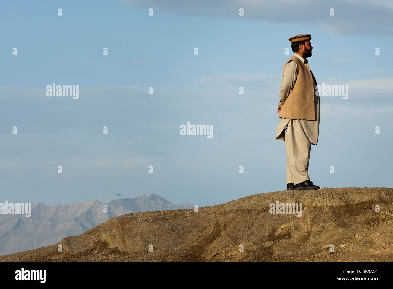 An Afghan man stands on a hill overlooking Kabul dressed in traditional clothes - Stock Image