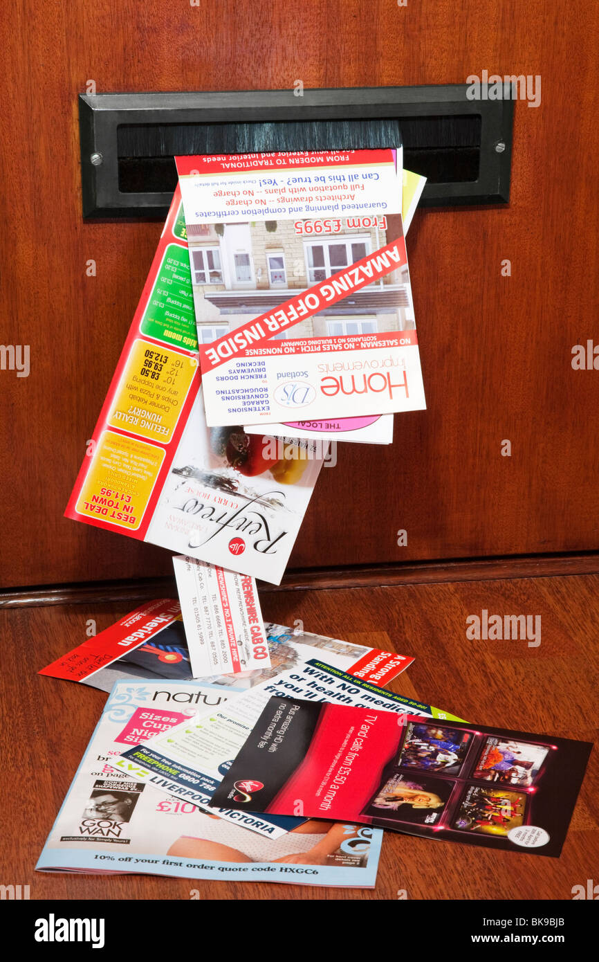 Unsolicited junk mail pushed through a letterbox. - Stock Image