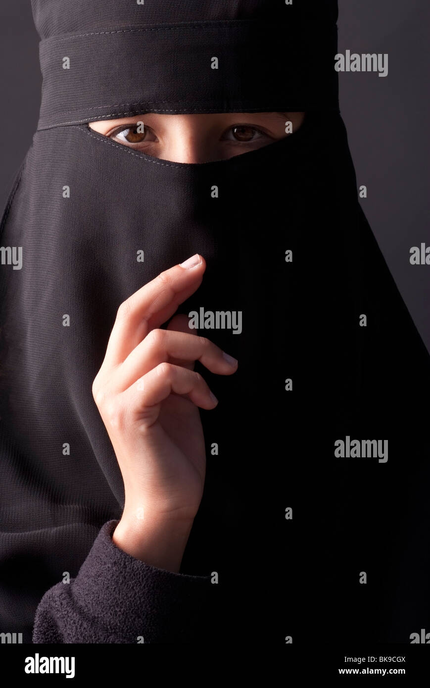 Teenage girl wearing a traditional Muslim niqab, a head covering with a veil that covers the face. - Stock Image