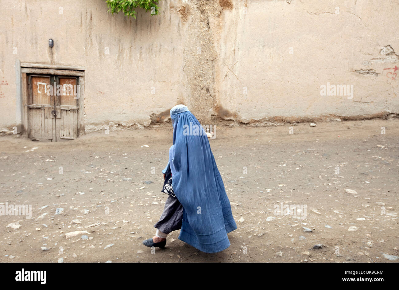 A burqua clad woman walks the laneways of Kabul Afghanistan. - Stock Image
