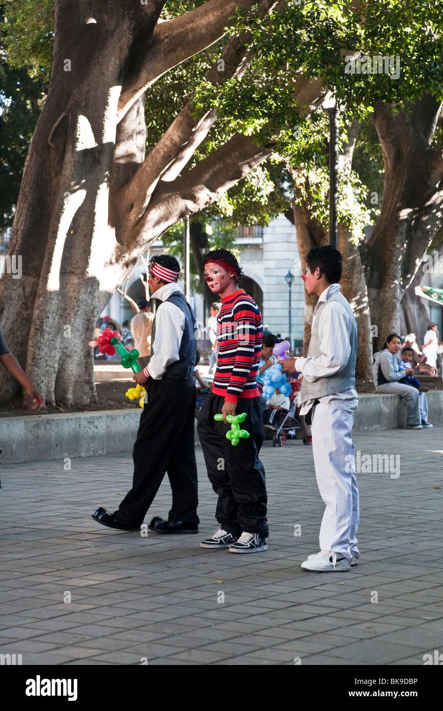 three Mexican teen boys in clown makeup selling fantasy balloon constructions in Oaxaca City Zocalo - Stock Image