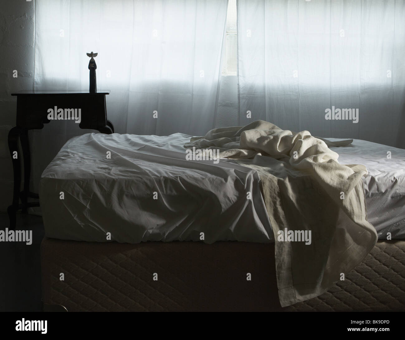 Unmade bed in morning light - Stock Image