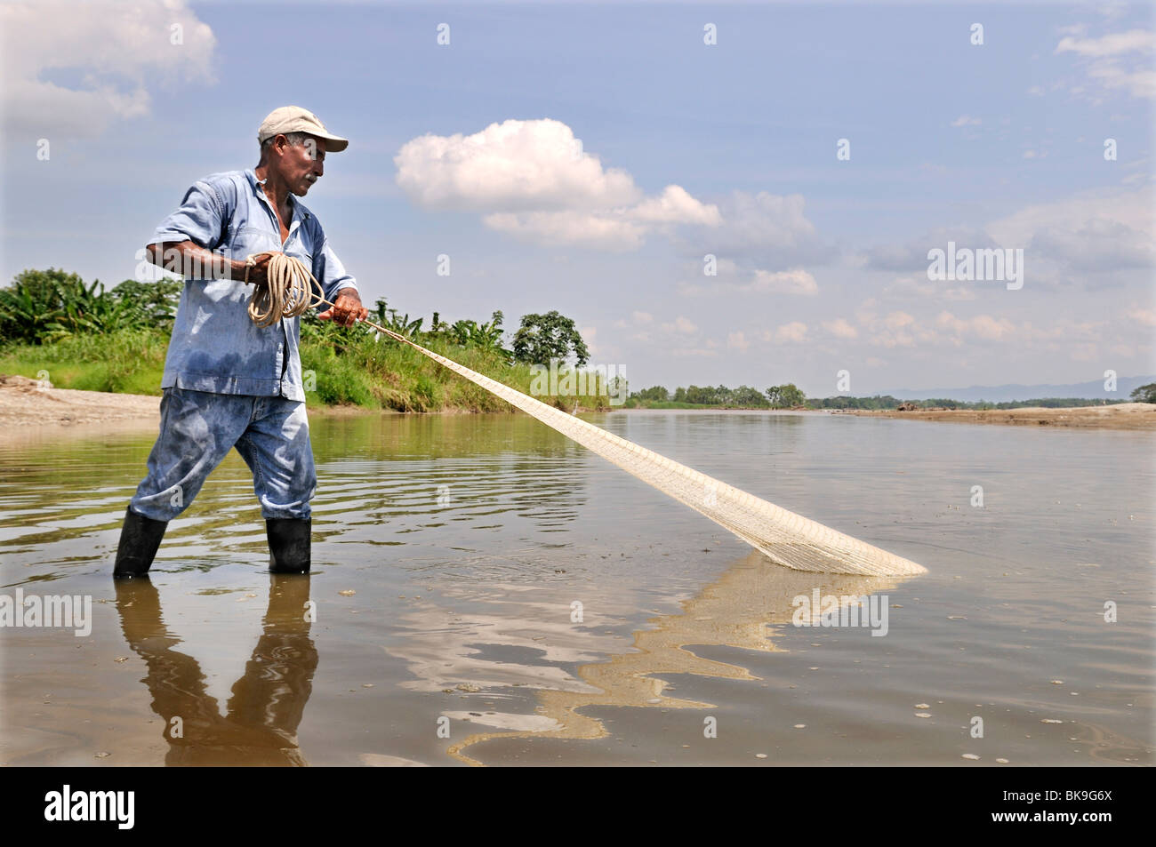Fisherman tossing a net into the Rio Magdalena River, La Dorada, Caldas, Colombia, South America - Stock Image