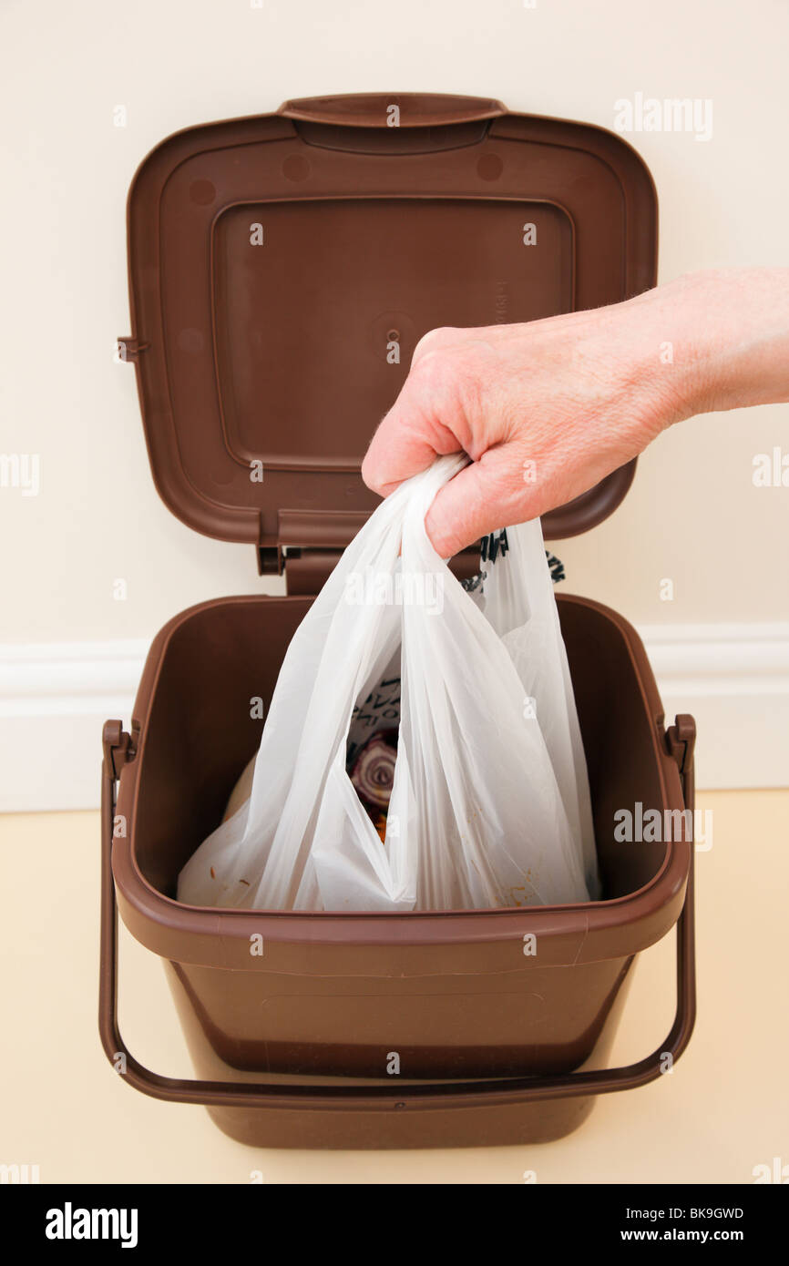 Person lifting plastic bag of household food waste out of indoor food waste bin inside. UK - Stock Image