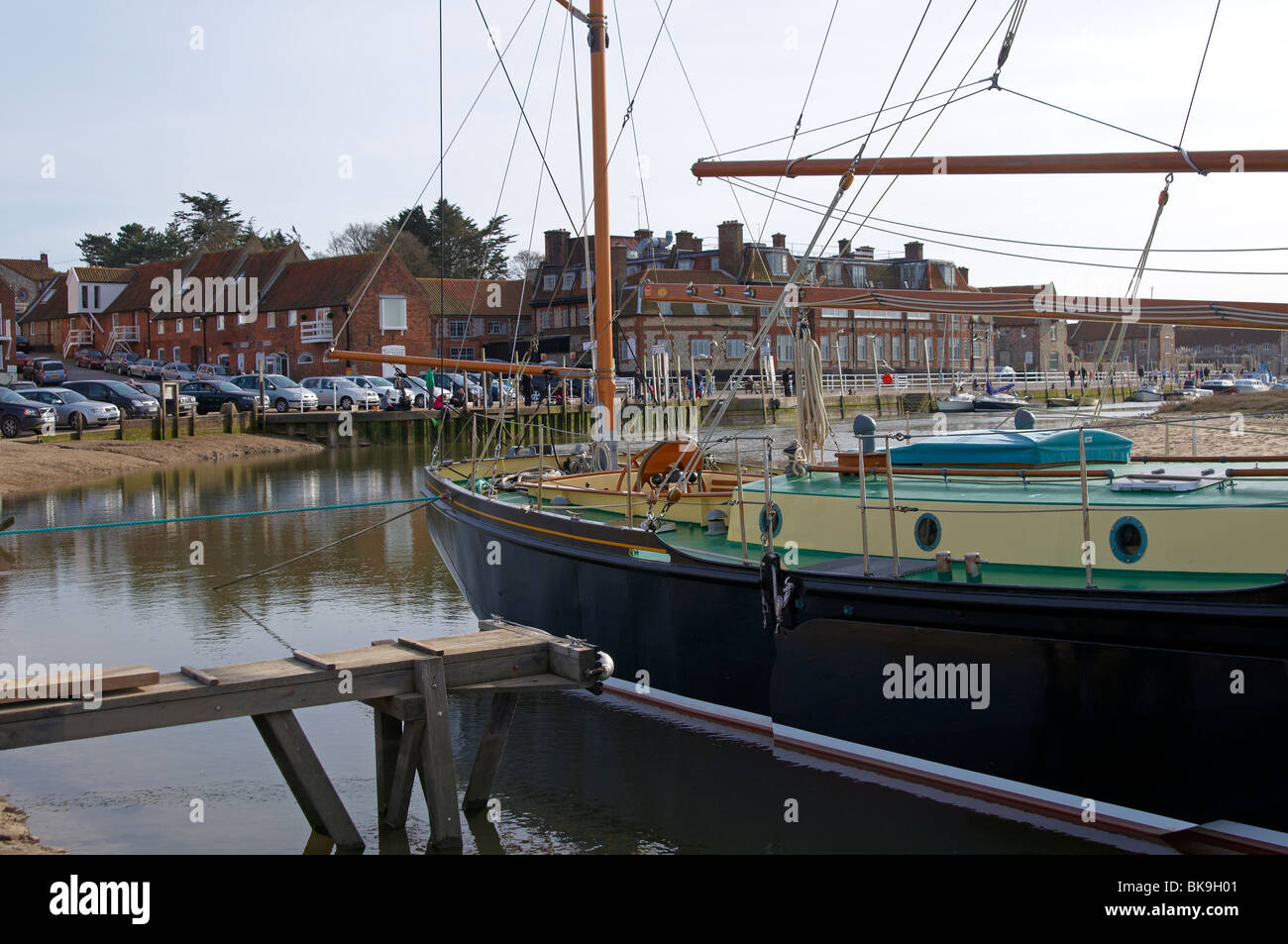 Blakeney harbour on the coast of North Norfolk with moored boats in the creek and against the quay. Stock Photo