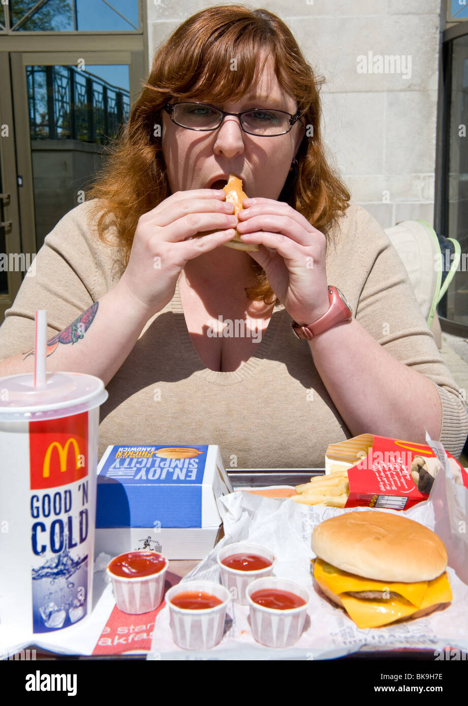 Overweight woman eating McDonald's fast food meal - Stock Image