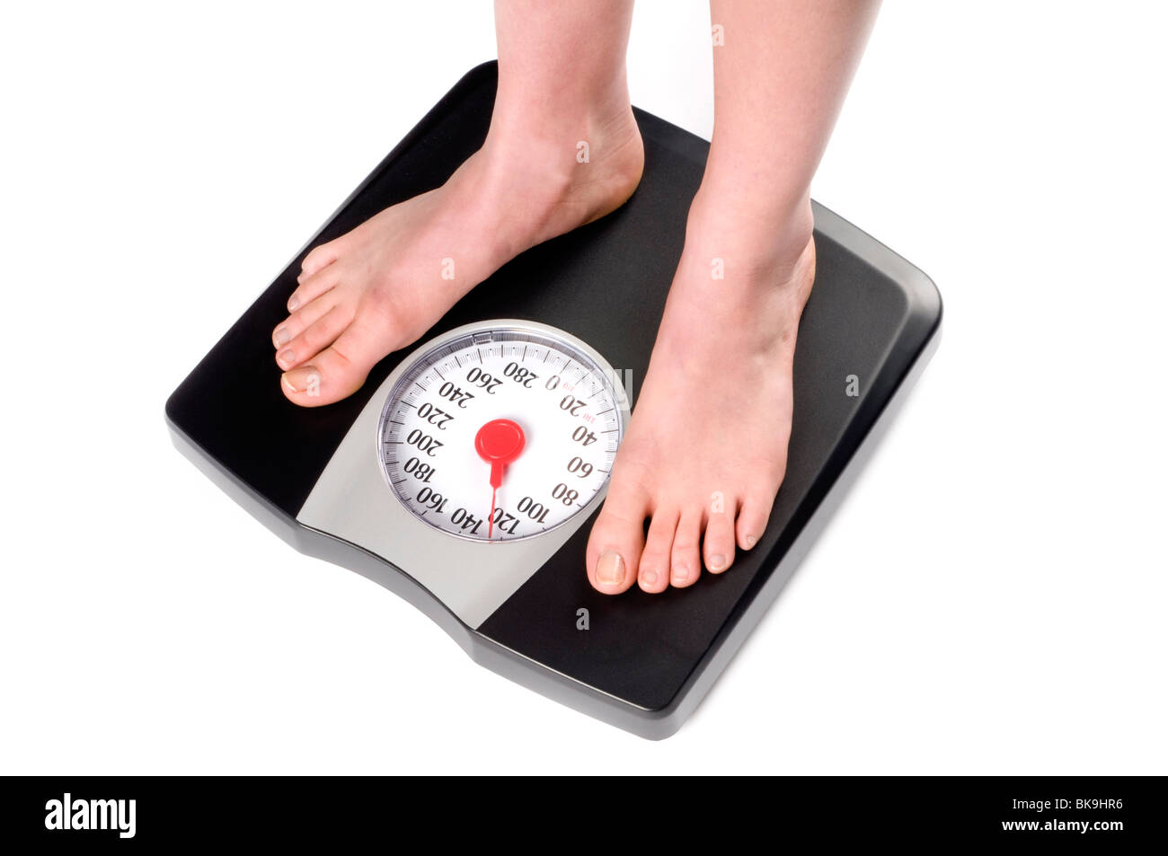 feet standing on weight scale - Stock Image