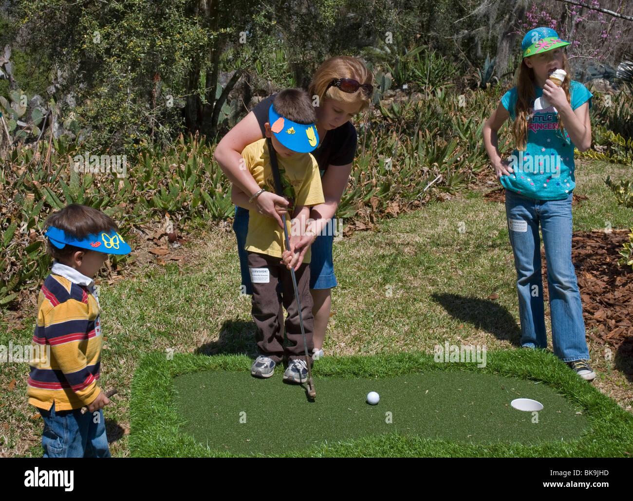 Kanapaha Spring Garden Festival Gainesville Florida teaching kids how to putt a golf ball - Stock Image
