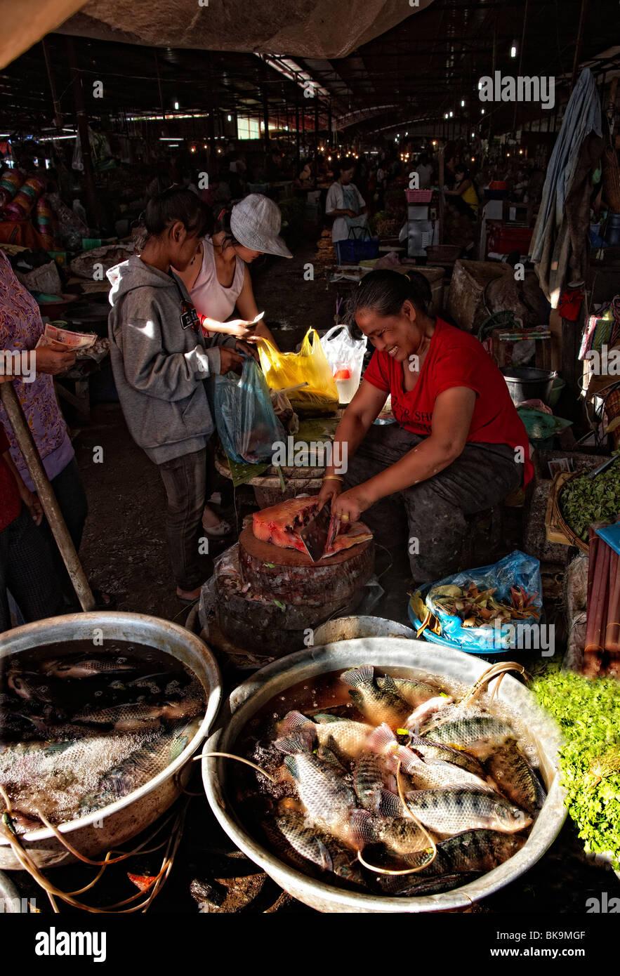 Woman fish seller cutting fish, food market, Vientiane, Laos - Stock Image