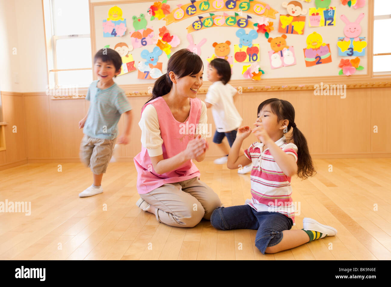 Nursery Teacher and Children Playing at Day-care Center - Stock Image