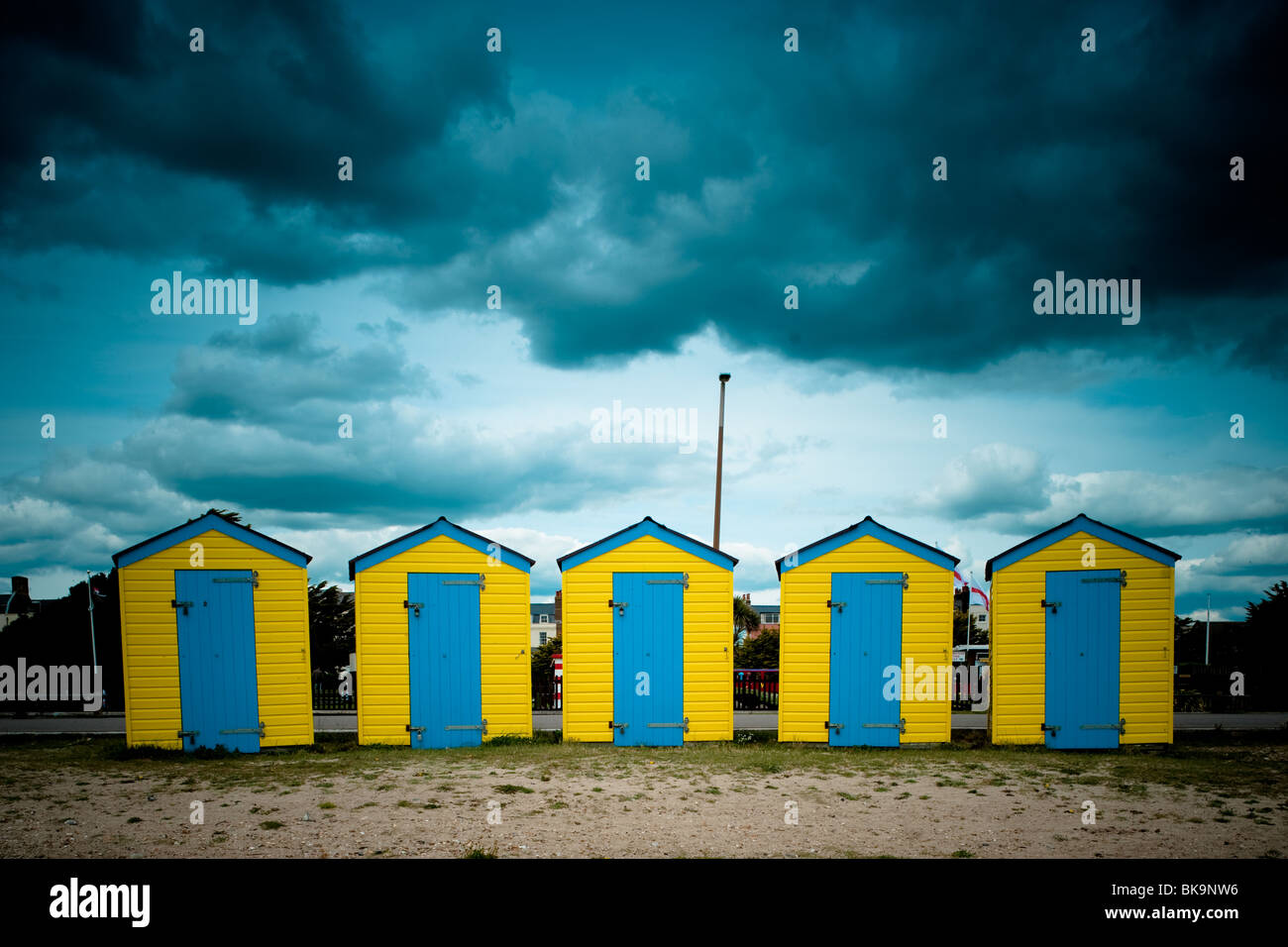 Yellow and Blue beach huts under a moody sky on Littlehampton beach, West Sussex Stock Photo
