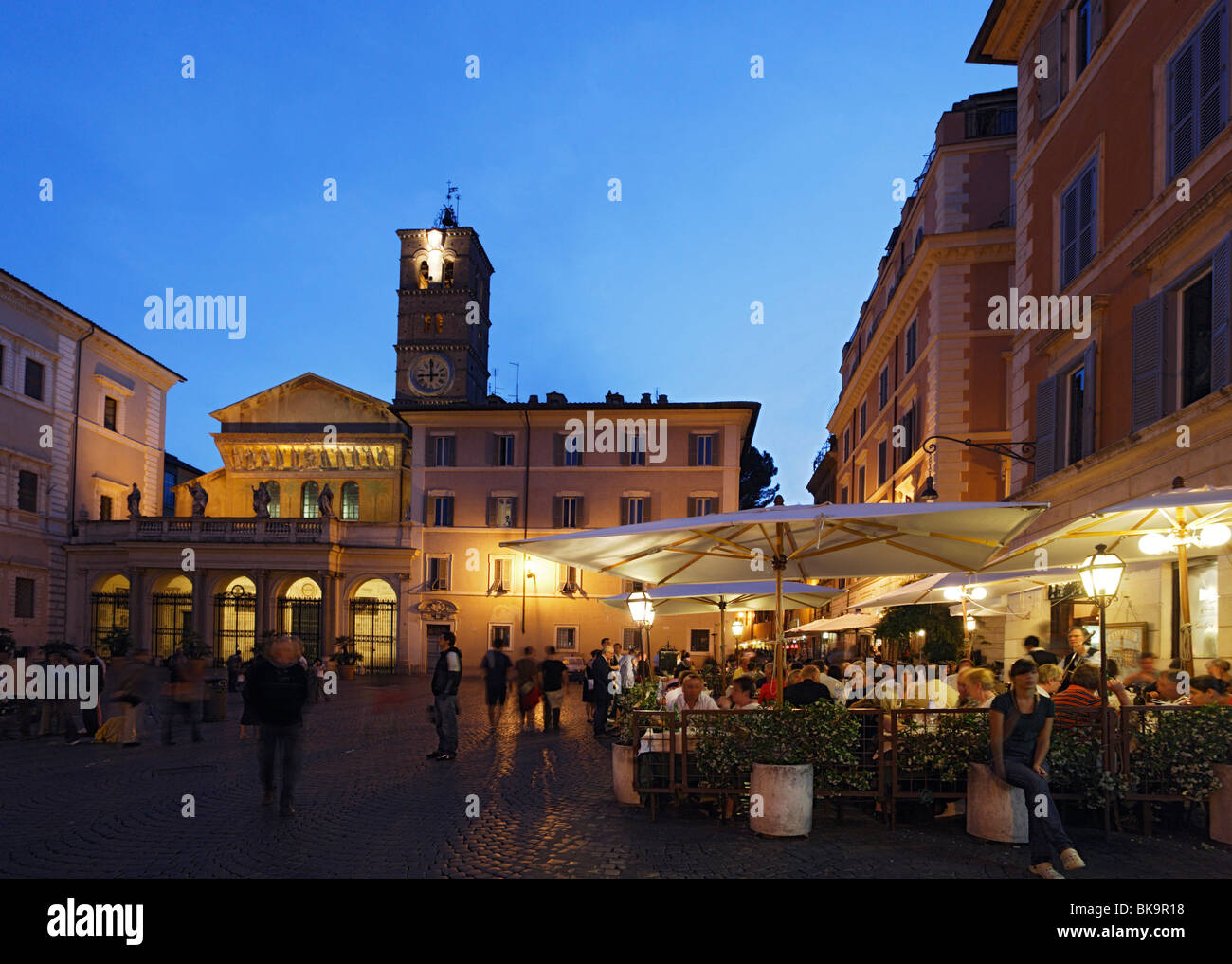 Guests in a pavement cafe, Santa Maria in Trastevere church in background, Rome, Italy - Stock Image