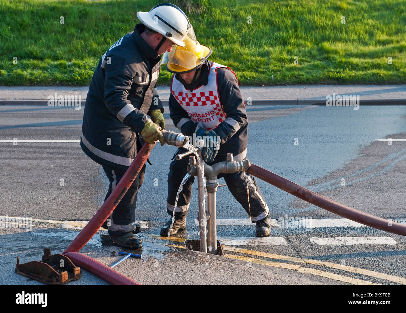Two firemen from the Mid-Wales Fire and Rescue Service connect hoses to a street hydrant - Stock Image