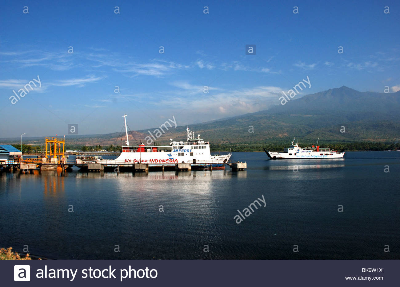Ferryboats at terminal with Gunung Rinjani volcano in background Kayangan Labuan Lombok Lombok Timur NTB Indonesia - Stock Image