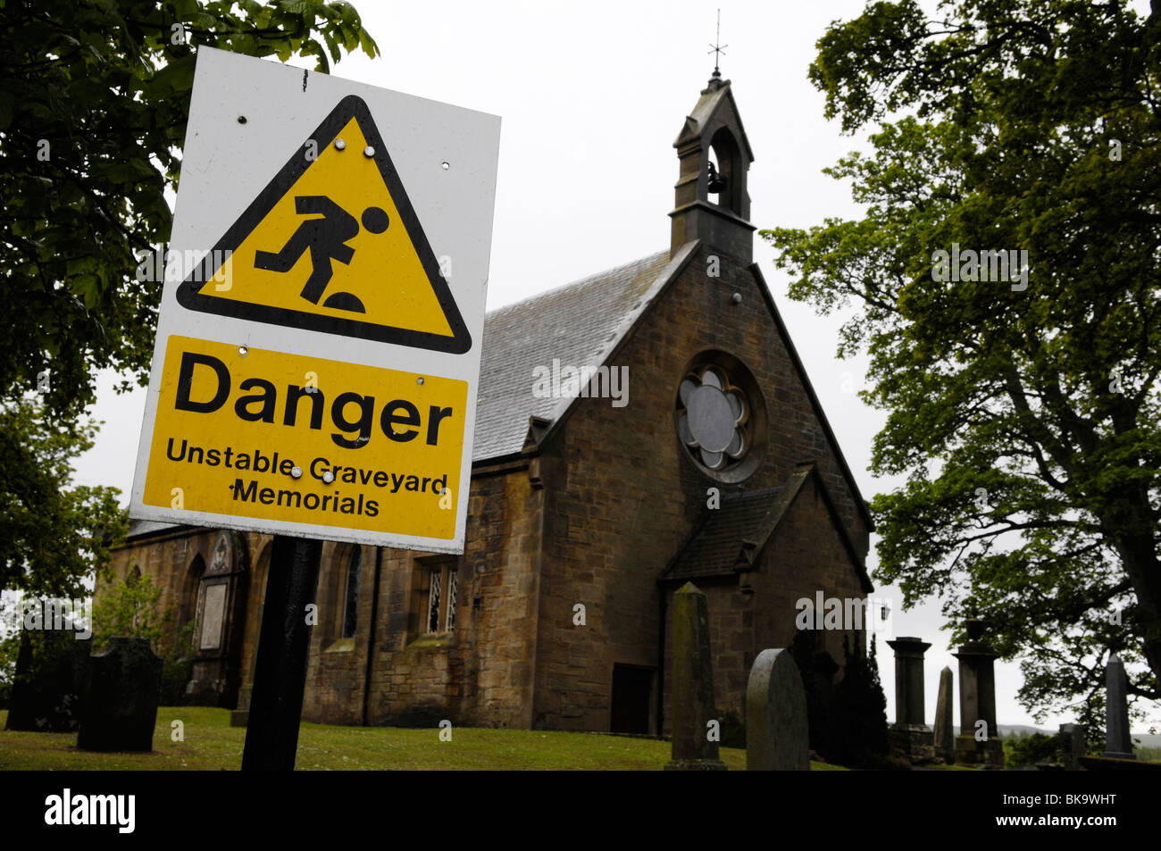 A sign in a church graveyard warns of unsafe headstones the sign says, Danger, unstable graveyard memorials. - Stock Image