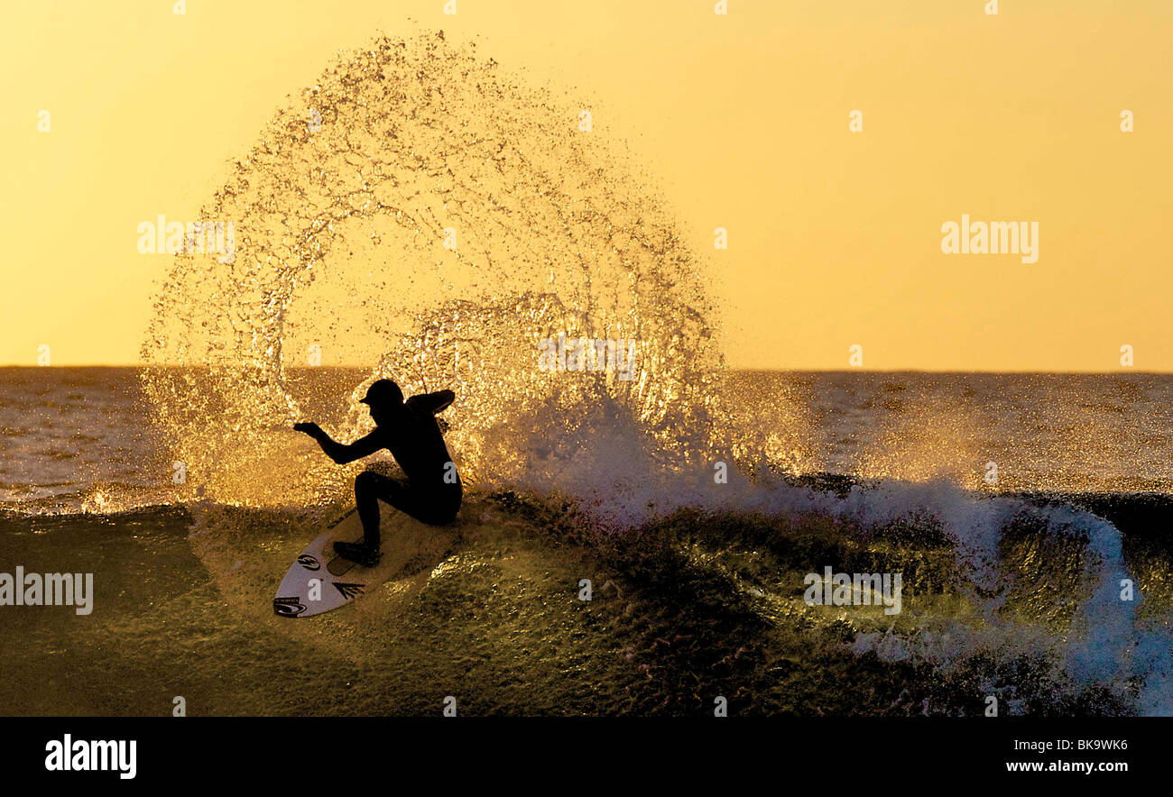 A surfer is silhouetted by the sun at Brims Ness, near Thurso, Scotland. The sun sets in the north of Scotland. Stock Photo