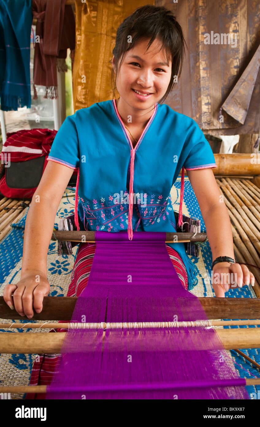 Young woman weaving cloth on loom; Patara Elephant Farm, Chiang Mai Province, Thailand. - Stock Image