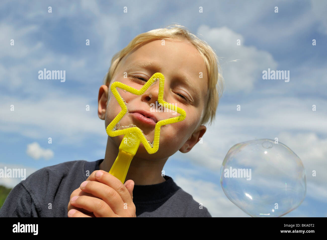 Boy blowing bubbles, Norrkoeping, Ostergotlands Lan, Sweden - Stock Image