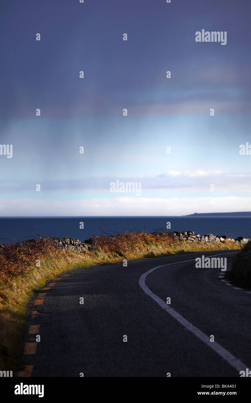 Early morning sunlight lights up the roadside in the Burren, Co. Clare on the West Coast of Ireland - Stock Image