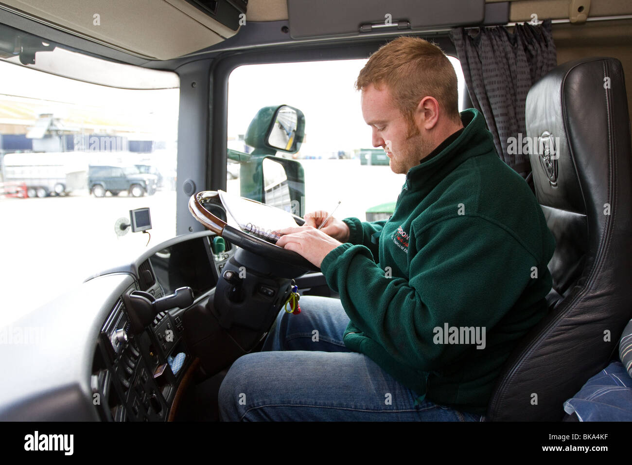 e75e3a440b A Lorry driver changing a tachograph card in his cab - Stock Image
