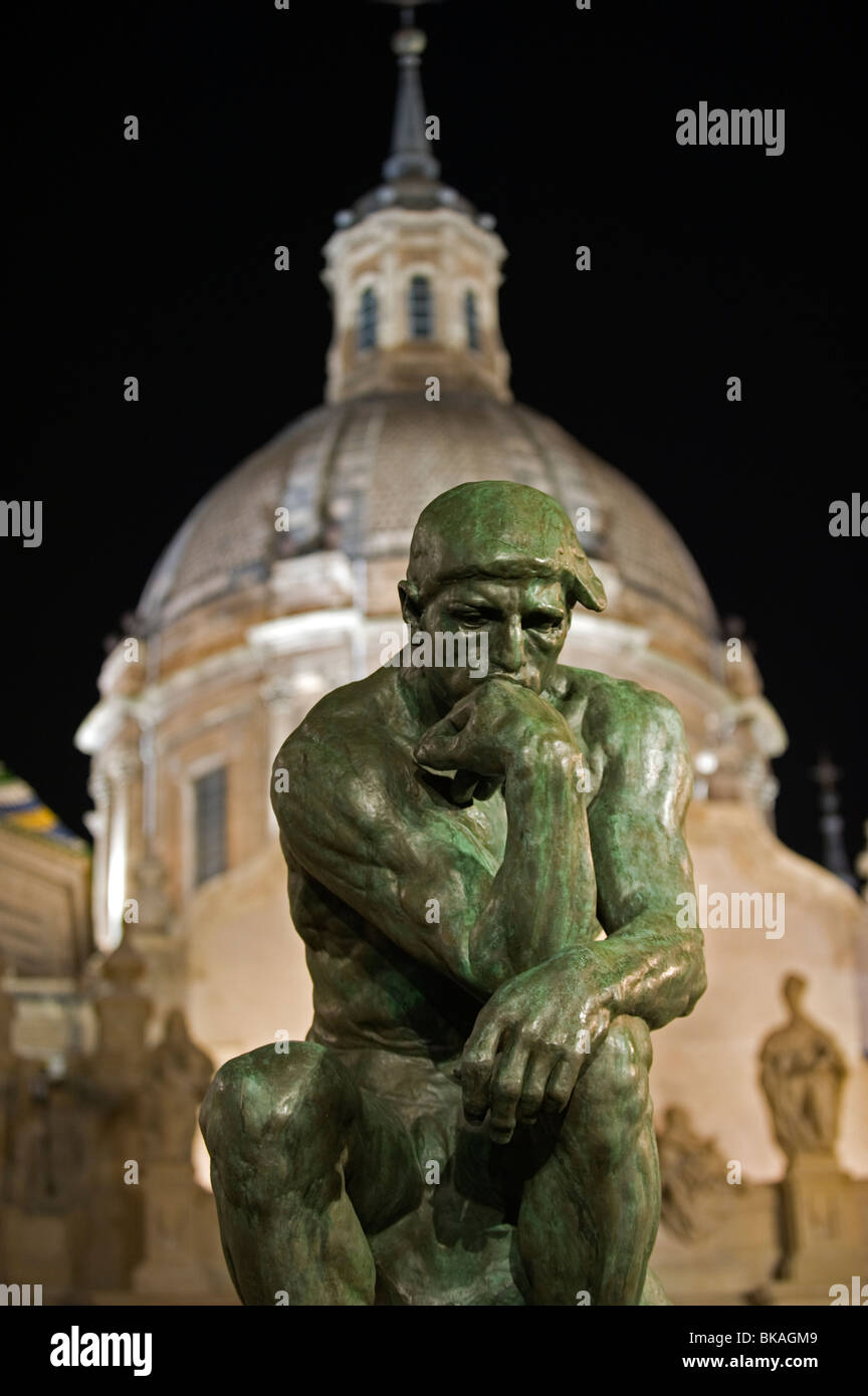 The Thinker Le Penseur by Auguste Rodin and Basilica Pilar, Zaragoza Spain. - Stock Image