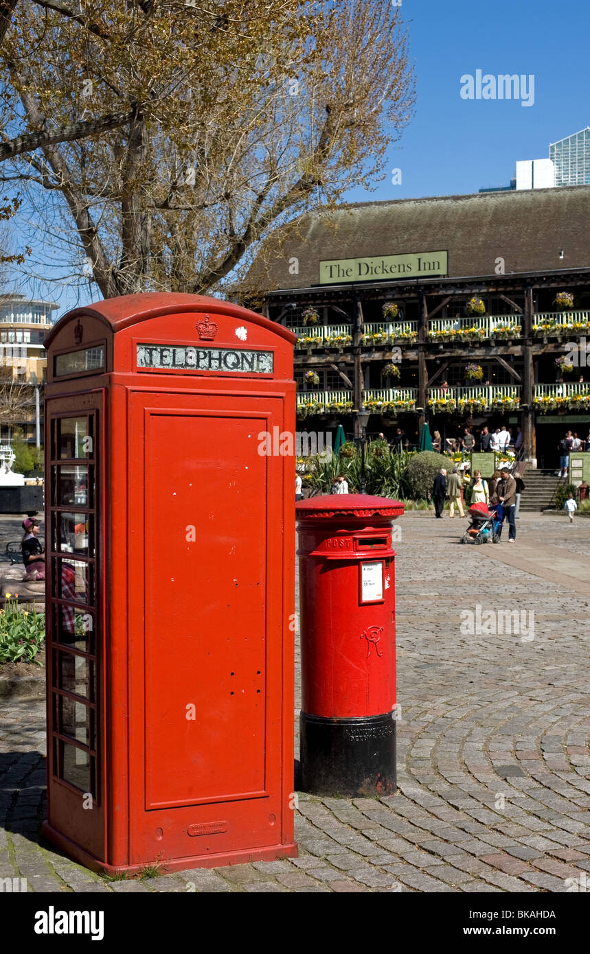 A traditional red telephone box and a letter box in the courtyard of the Dickens Inn pub in London.  Photo by Gordon - Stock Image