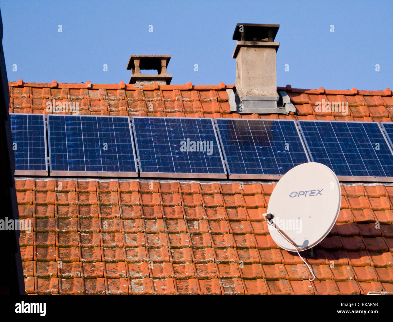 French solar panel / panels and satellite / TV dish on the roof of a farm house in Alpine / Alps region of Savoy, - Stock Image