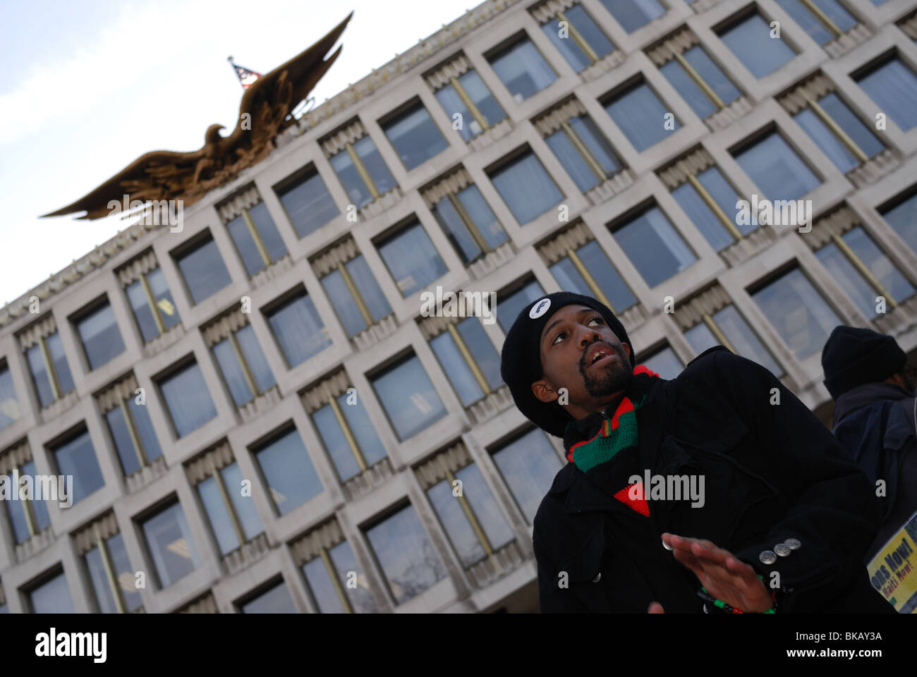 A Haitian man stands outside the US Embassy in London during a protest demanding justice for Haiti. Stock Photo