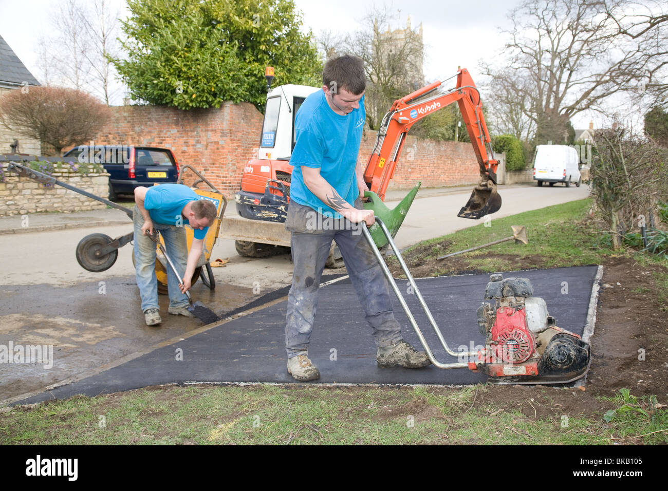 Road workers laying a tarmac driveway - Stock Image