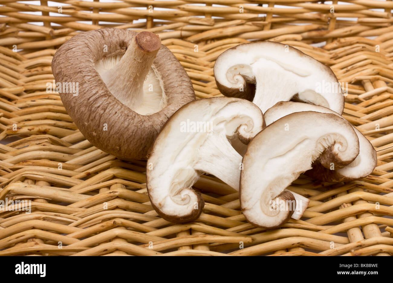 Whole and sliced raw Shiitake Mushrooms against wicker basket. - Stock Image