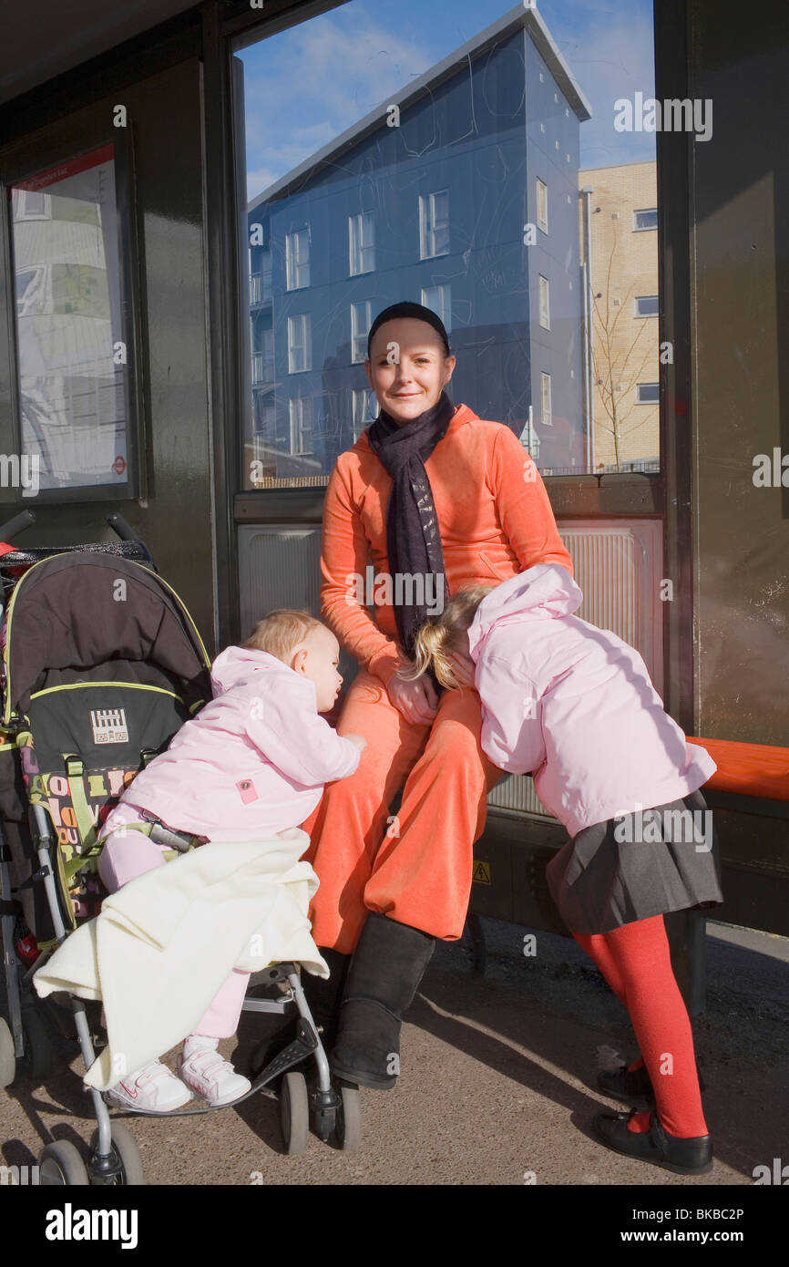 A mum in an orange tracksuit waits for the bus with her two daughters. - Stock Image